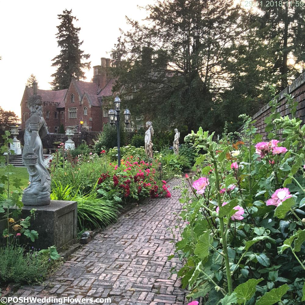Thornewood Castle garden path blooming with Hollyhocks